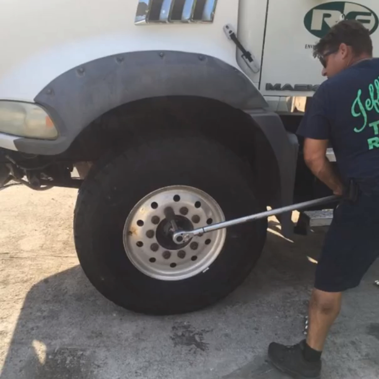 Jeff Personette using lug wrench on a truck tire